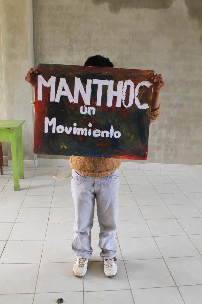 Ein Junge hält ein Plakat der Bewegung für arbeitende Kinder und Jugendliche